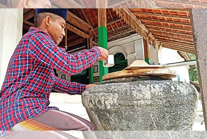 TEGUK : Santri Ponpes Mahir Arriyadl meminum air dari gentong kuno di masjid pondok.