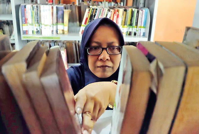 TELITI: Kasi Pembinaan Perpustakaan Kota Kediri Dyah Nurwahyuni menata koleksi buku di Perpustakanan Umum Kota Kediri Jumat (11/9).