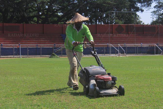 TETAP DIRAWAT : Pengelola Stadion Brawijaya Purwanto melakukan pemotongan rumput lapangan beberapa waktu lalu. Saat ini, stadion tersebut disewakan untuk masyarakat.