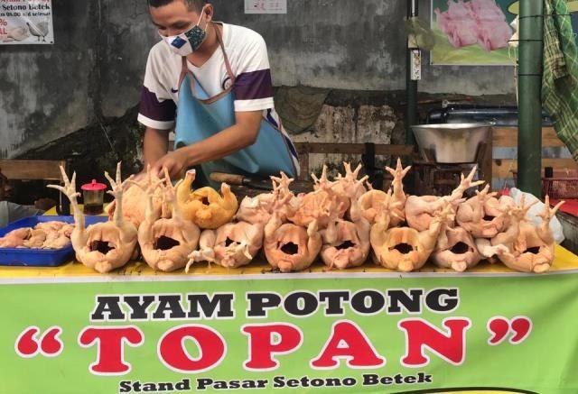 BELUM ADA LONJAKAN: Taufan Akbar, pedagang daging ayam, di lapaknya di Pasar Setonobetek (18/3).