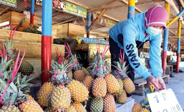 NAIK DUA KALI: Penjual nanas di kawasan wisata Gunung Kelud yang masih bertahan melayani pembeli kemarin.