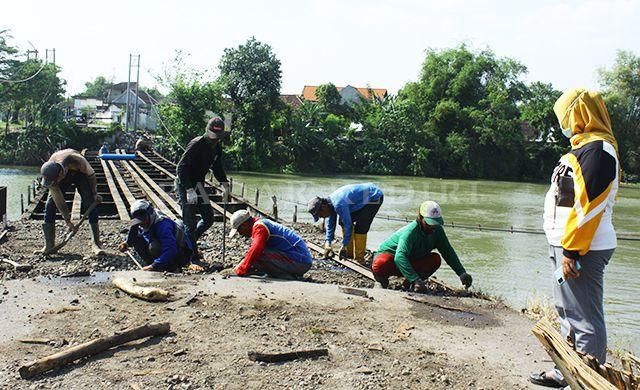 BESI TUA: Pekerja melakukan pembongkaran Jembatan Mrican kemarin.