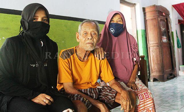 MENUNGGU LAMA: Syamsul Muanam diapit Siti Komariah (kiri) dan istrinya, di tempat tinggalnya, di Desa Ngadiluwih.