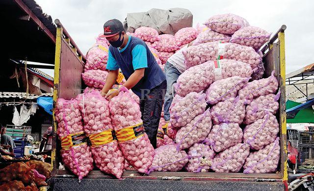 MENUMPUK : Seorang pekerja menurunkan bawang putih dari truk pengangkut di Pasar Grosir Ngronggo kemarin.