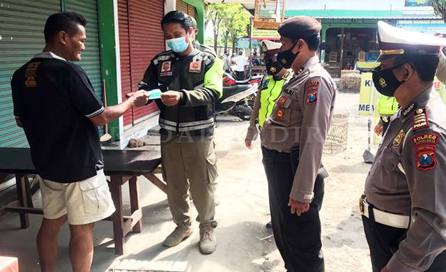 OPERASI YUSTISI: Tim gabungan satpol PP, Polri, dan TNI memberi masker di Pasar Banjaran, Kecamatan Kota Kediri.