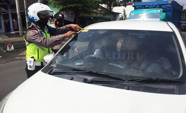 PASTIKAN AMAN: Anggota Satlantas Polres Kediri memberi stiker bebas Covid-19 di kendaraan yang melewati pos penyekatan Kandangan (30/5).