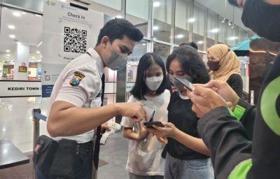 BINGUNG: Petugas keamanan mal membantu calon pengunjung yang akan menggunakan aplikasi PeduliLindungi sebelum masuk ke Kediri Town Square kemarin.