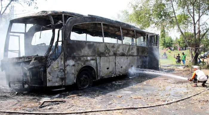 TINGGAL KERANGKA: Petugas pemadam kebakaran berusaha memadamkan api yang melalap bus di bengkel las di Desa Tanjungrejo, Dawe, Kudus, kemarin.