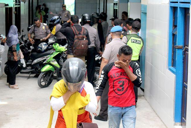 SEMBUNYIKAN MUKA: Salah satu pasangan bukan suami istri yang terjaring saat Operasi Pekat Cipta Kondisi di kos Kota Purwodadi kemarin.