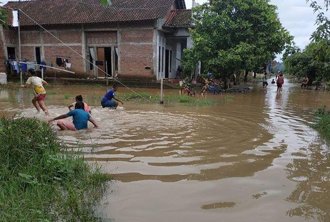 BERMAIN: Anak-anak bermain air genangan banjir di sekitar persawahan dan pemukiman warga Desa Batukali, Kalinyamatan kemarin.