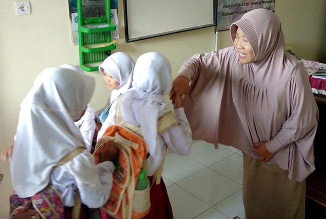PEDULI: Suharti menyambut salam para siswa di Desa Tegaldowo, Kecamatan Gunem, Rembang, baru-baru ini.