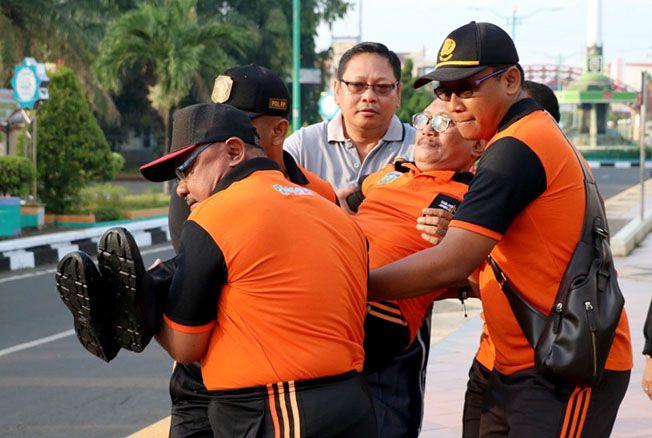 DIDUGA SERANGAN JANTUNG: Kepala Dinas Pariwisata dan Kebudayaan Jepara Basuki Wijayanto dibopong beberapa pejabat setelah menghentikan bacaan laporan penyelenggaraan HUT ke-470 di Alun-alun Jepara kemarin.