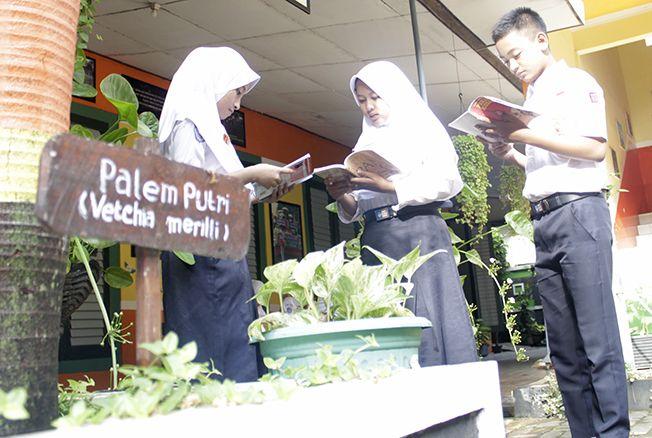 HIJAU: Sejumlah murid membaca buku di halaman sekolah yang asri.