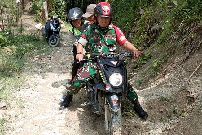 MEDAN BERAT: Babinsa Jambangan Koramil 09/Gundih bersama warga kompak bahu-membahu menuju lokasi TPS.