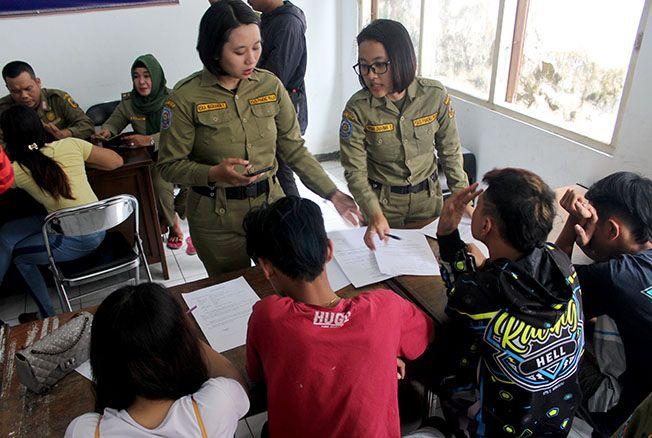 Petugas Satpol PP sedang melakukan pendataan kepada muda-mudi yang diamankan dalam razia tempat kos pagi kemarin.