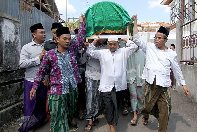 PENGHORMATAN TERAKHIR : Puluhan santri sedang memanggul jenazah KH. Munir Hasyim. Mereka memberikan penghormatan terakhir dengan mengantarkannya hingga ke pemakaman makam keluarga Mbah Abu Bakar, Bakalan Krapyak, Kudus kemarin (13/05).