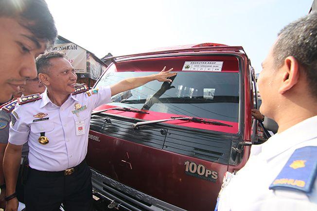 LAYAK JALAN: Kepala Dishub Kudus Abdul Halil menempelkan stiker layak jalan pada kendaraan angkutan kemarin.