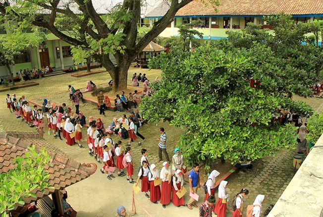 MENGULAR: Sejumlah anak-anak SD didampingi orang tua antre mendaftar sekolah di SMPN 2 Rembang kemarin. Mereka rela datang subuh demi dapat daftar di sekolah favorit.