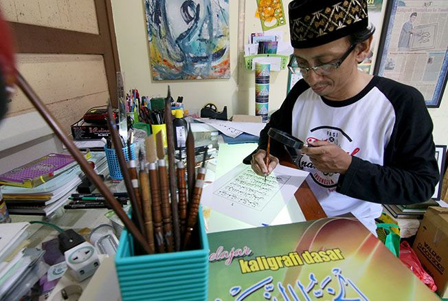 DIBANTU KACA PEMBESAR: Muhammad Syukron sedang menulis Qiroati di kediamannya kemarin. Dia pernah menulis Alquran untuk percetakan.
