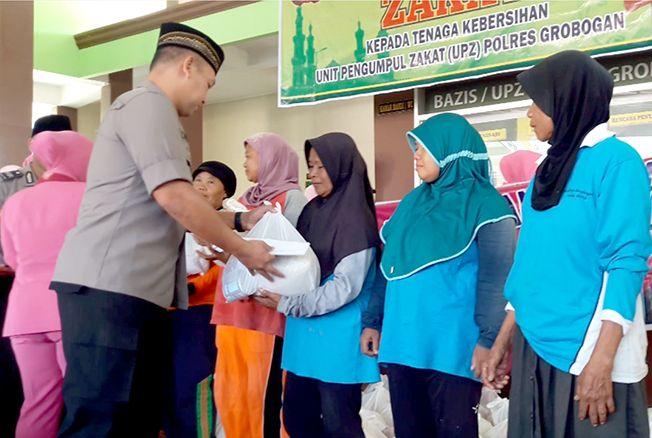 SERAHKAN BANTUAN: Kapolres Grobogan AKBP Choiron El Atiq menyerahkan bantuan sembako kepada petugas kebersihan kota Purwodadi di masjid Mapolres setempat.