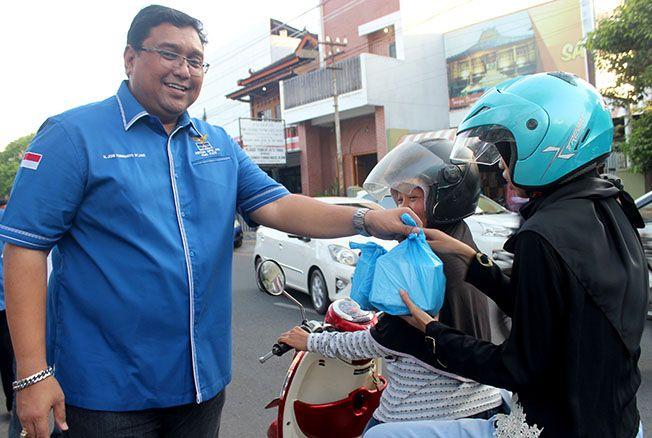 BAGIKAN TAKJIL: Ketua DPC Partai Demokrat memberikan takjil kepada para pengendara yang melintas di Jalan Dr Wahidin kemarin.