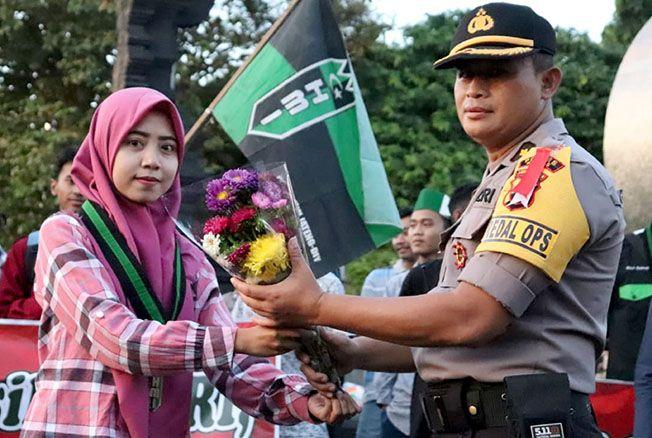 AKSI DAMAI: Perwakilan mahasiswa yang tergabung dalam Himpunan Mahasiswa Indonesia (HMI) Cabang Kudus memberikan buket bunga kepada Kabag Ops Polres Kudus Kompol Jodi Setyo Margono dalam aksi damai di Alun-alun Simpang Tujuh kemarin.