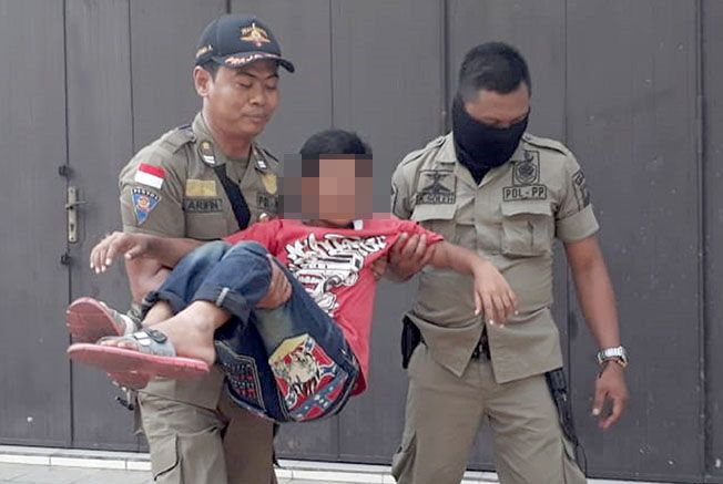 MELANGGAR PERDA: Tim operasi penegakkan perda Satpol PP Kudus saat mengamankan para anak-anak penjual rujak di kawasan traffic light pentol.