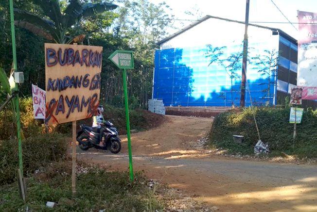 PROTES: Spanduk penolakan yang dipasang warga di sekitar kandang ayam di RT 1/RW I, Desa Somosari, Kecamatan Batealit. Warga protes karena bau memyengat dari kandang ayam menganggu aktivitas warga.