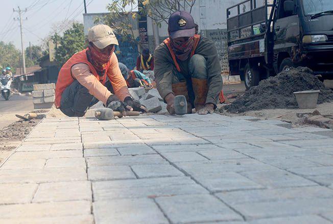 DIKEBUT: Para pekerja peningkatan jalan nasional Jepara memasang paving untuk pembuatan trotoar di sepanjang jalan nasional ruas Lebuawu, Pecangaan.