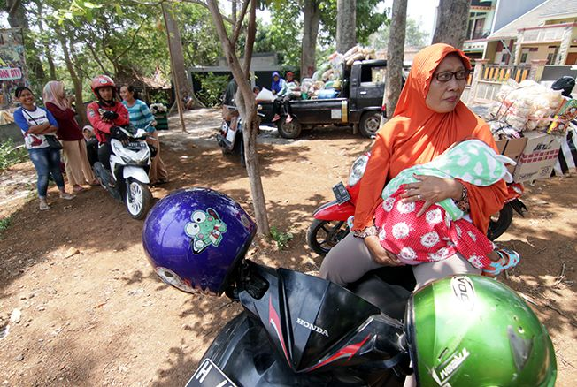MENUNGGU PENGASPALAN: Warga harus bersabar dan tertahan sementara menunggu pengaspalan jalan menuju Desa Rahtawu selesai kemarin.