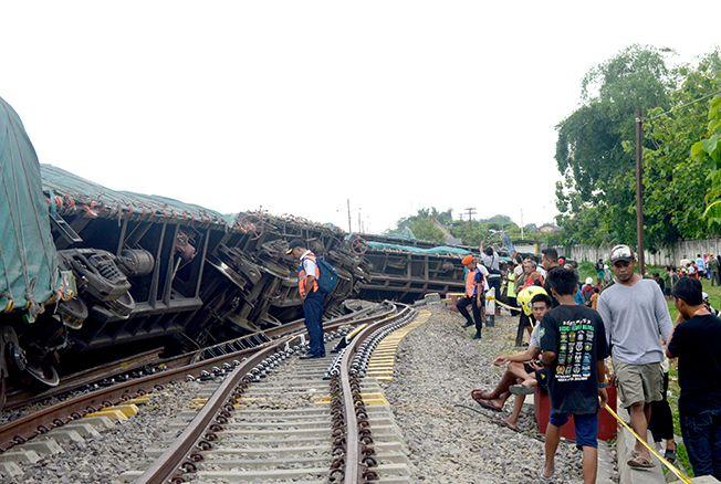 JADI TONTONAN: Personel Daop 4 PT KAI Semarang mengecek gerbong kereta yang terguling di jalur II Stasiun Doplang, Kabupaten Blora, kemarin siang.