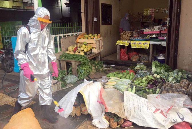 PERANGI COVID-19: Petugas menyemprotkan disinfektan di pasar tiban Desa Nganguk yang diinisiasi PT Nojorono Tobacco International (PT NTI) dan bekerja sama dengan sejumlah Instansi di Kabupaten Kudus.