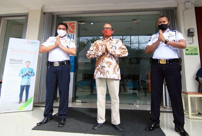 SAMBUT NASABAH: Branch Manager PT Bank BNI Syariah Cabang Kudus Hadi Suseno (tengah) menyambut dan melayani nasabah sesuai dengan protokol kesehatan.