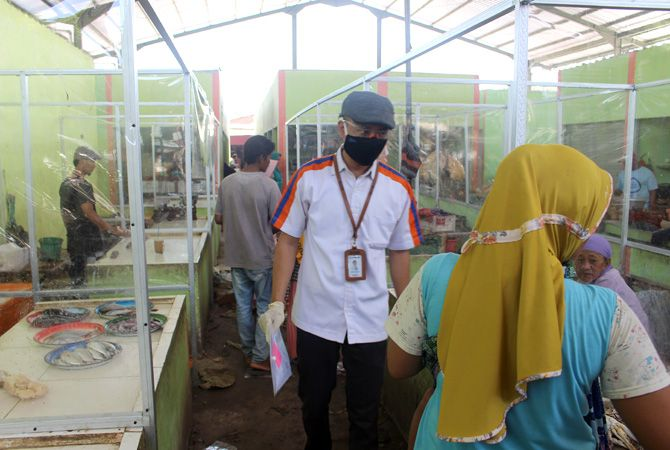 PROTOKOL KESEHATAN: Mantri BRI menggunakan atribut sesuai protokol kesehatan, menggunakan masker, sarung tangan dan kacamata dalam menjalankan tugasnya dalam melayani nasabah.