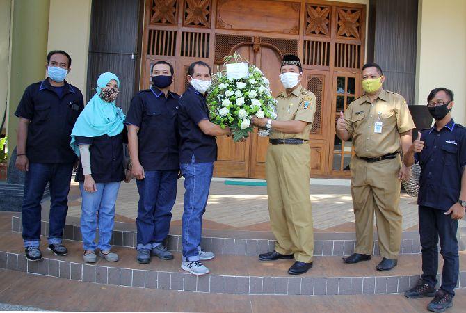 KOMPAK: Direktur Jawa Pos Radar Kudus Baehaqi menyerahkan bunga ucapan HUT kepada Bupati Rembang Abdul Hafidz didampingi Kepala Bagian Protokol dan Komunikasi Pimpinan Daerah Arief Dwi Sulistiya di rumdin kemarin.