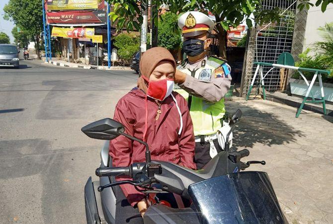 AYO TERTIB: Anggota Satlantas Polres Jepara memakaikan masker kepada pengendara.