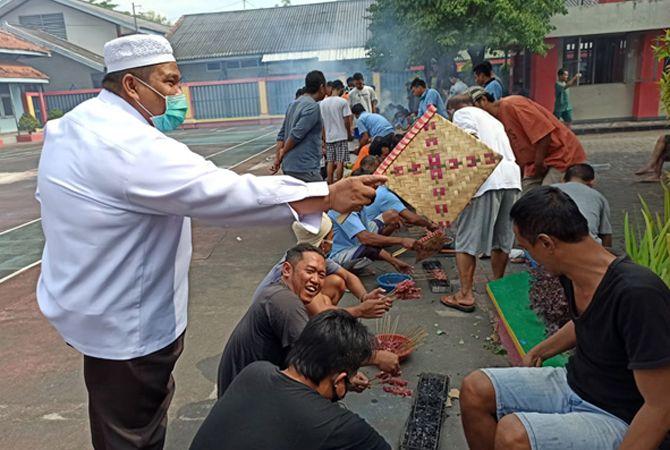 KEBERSAMAAN: Kepala Rutan Kelas II B Jepara Heru Yuswanto (berdiri) bersama warga binaan nyate bareng usai memotong sapi kurban kemarin.