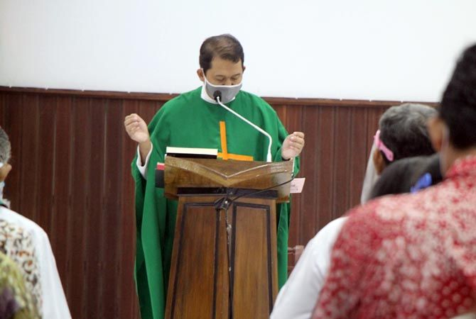 PAKAI MASKER: Romo Fransiscus Soni Apri Untoro Nugroho memimpin misa perdana di Gereja Katolik Santo Petrus dan Paulus Rembang kemarin.
