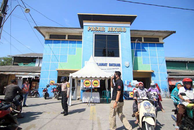 TELAH DIBUKA: Polisi mengatur arus lalu lintas di depan Pasar Jekulo belaum lama ini. Dua pintu barat dan timur pasar itu kembali dibuka.