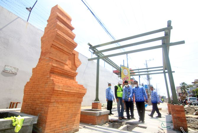 PENGERJAAN SESUAI: Pegawai Dinas PUPR Kudus mengecek pengerjaan city walk di Jalan Sunan Kudus kemarin siang.
