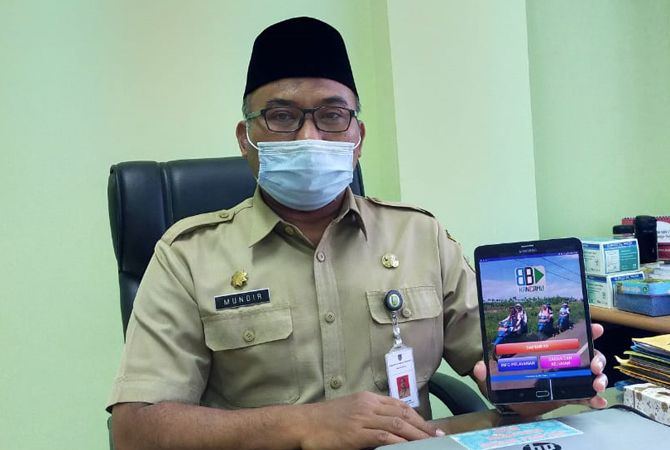 INOVASI BARU: Kepala Dinas Sosial P3AP2KB Kudus Mundir memperlihatkan aplikasi Kancamu di ruangan kerjanya kemarin.