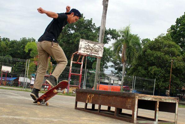 STANDING: Satu sisi papan skateboard terangkat saat Uud memperagakan trik.
