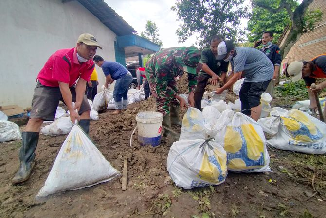 SENGKUYUNG: Sejumlah personel TNI-Polri dan masyarakat bergotong-royong memperbaiki dengan membuat tanggul darurat dengan karung berdiri tanah padas kemarin.