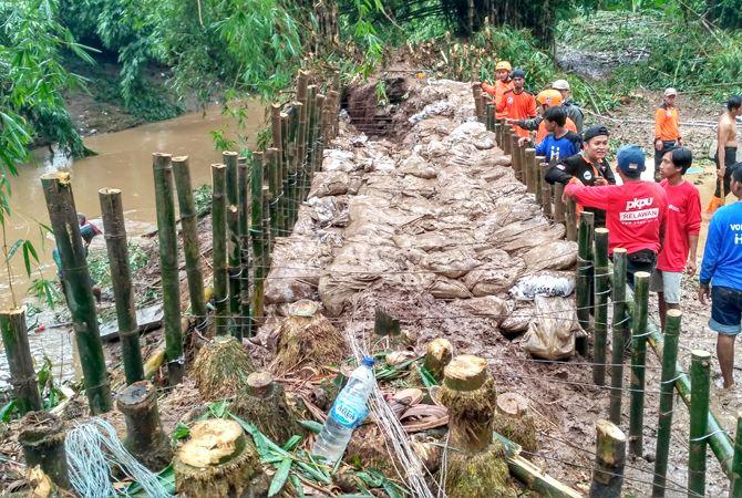 KERJA SAMA: Berbagai pihak kebut penambalan tanggul di dua titik di Desa Tenggeles, Mejobo, Kudus, kemarin.