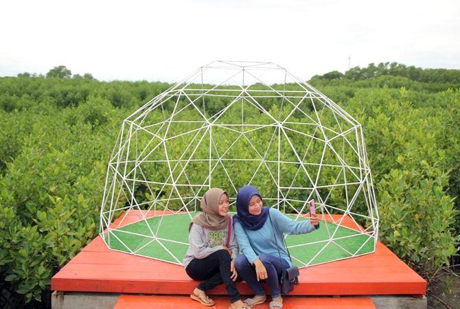 JEMBATAN MERAH: Sejumlah wisatawan menikmati fasilitas menikmati destinasi wisata di jembatan merah mangrove Pasar Mbaggi Rembang belum lama ini.