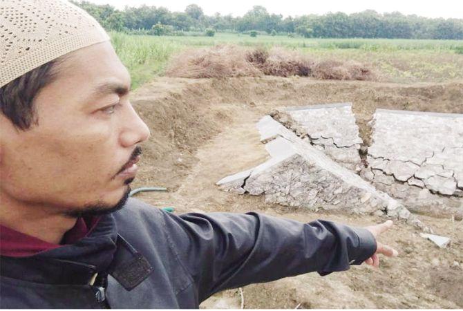 DITINJAU: Seorang staf Kecamatan Pamotan mengecek kondisi embung Gegersimo yang ambyar.