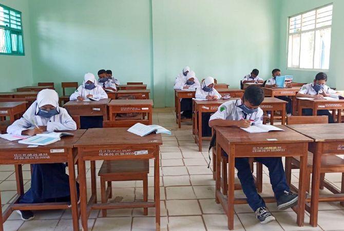 PATUHI PROKES: Anak-anak SMPN 1 Kragan mematuhi prokes pencegahan Covid-19 saat hendak masuk di sekolahnya.