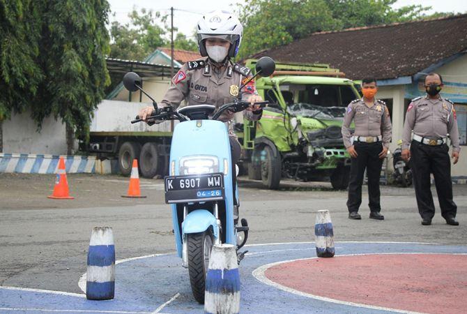 UJI KETANGGUHAN: Seorang polwan di jajaran Satlantas Polres Rembang uji coba naik motor listrik di halaman kantornya kemarin.
