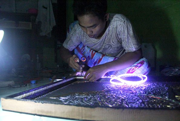 LEMBUR: Salah satu santri membuat kaligrafi elektronik hingga larut malam.