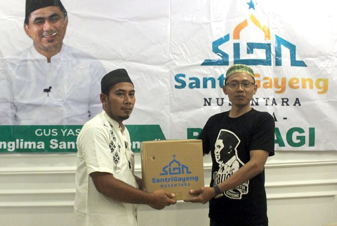 BANTU SESAMA: Korkab Santri Gayeng Nusantara Jepara KH. Fathur Rohman (kanan) menyerahkan secara simbolis paket sembako kepada perwakilan korcam Santri Gayeng Nusantara Jepara.
